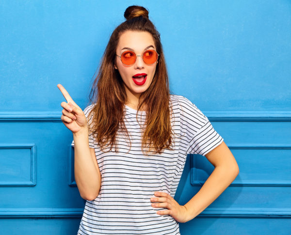 Girl model in casual summer clothes with red lips, posing near blue wall. Gets good idea in mind how improve project, raises finger, wants to sound and express thoughts